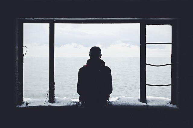 窓辺で悩む男性の後ろ姿