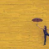 ポジティブに傘を広げる女性とキレイな壁