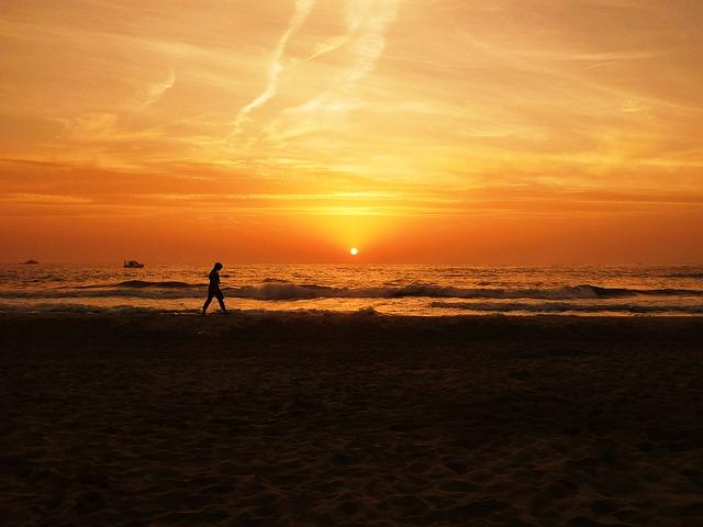 1人で砂浜を歩く人と夕焼け
